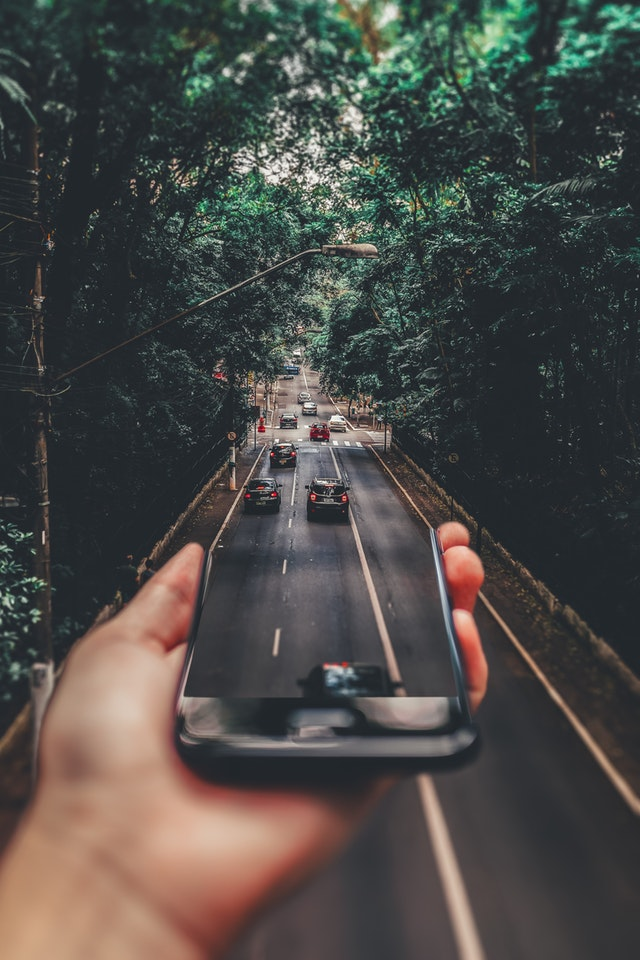 How to purchase your first vehicle - Leave The Costs Behind You On The Road - image of smartphone and traffic