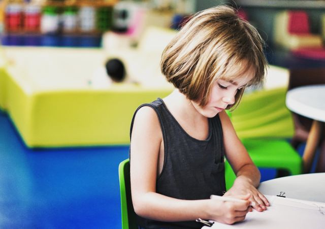 Explaining business to kids - entrepreneurship and family image of young girl at a desk