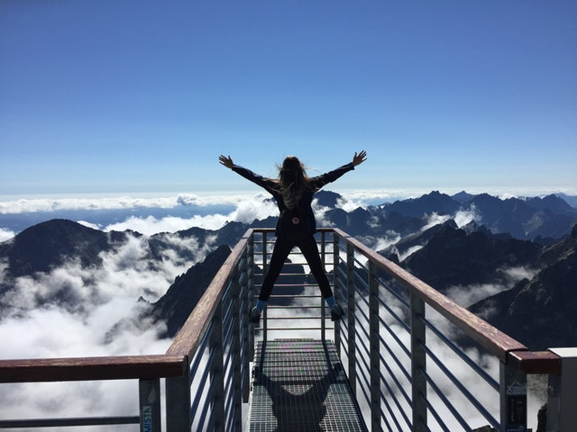How To Invest In Yourself And Your Future - image of girl on mountain top, freedom success celebration
