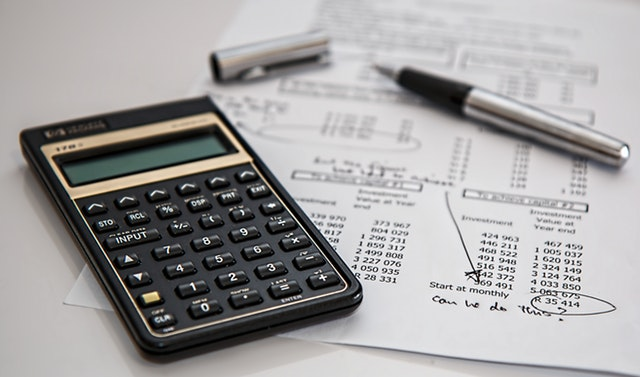 Personal Finance Tips for Business Owners - calculator and financial papers image