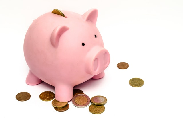 Tips To Be More Financially Successful In Life - piggy bank saving coins image