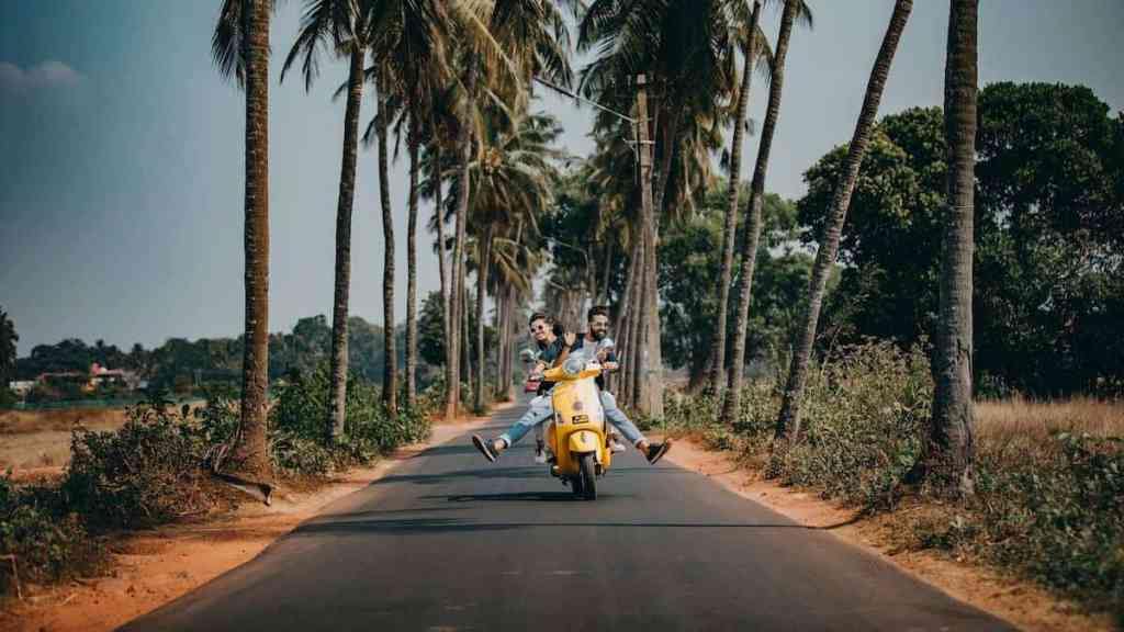 man and woman on a scooter traveling on a budget and not breaking the bank