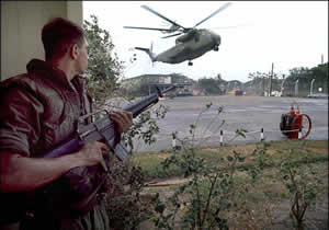 A Marine provides security as Sikorsky CH-53 helicopters land at the Defense Attaché Office compound. Via Wikimedia Commons. Image Author: Dirck Halstead