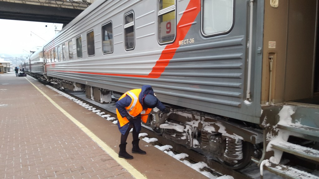 The provodnik carries out one of her duties during halts at stations: knocking the snow from the train's uncarriage