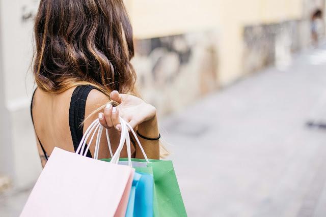 Jeune femme qui tient plusieurs sacs shopping