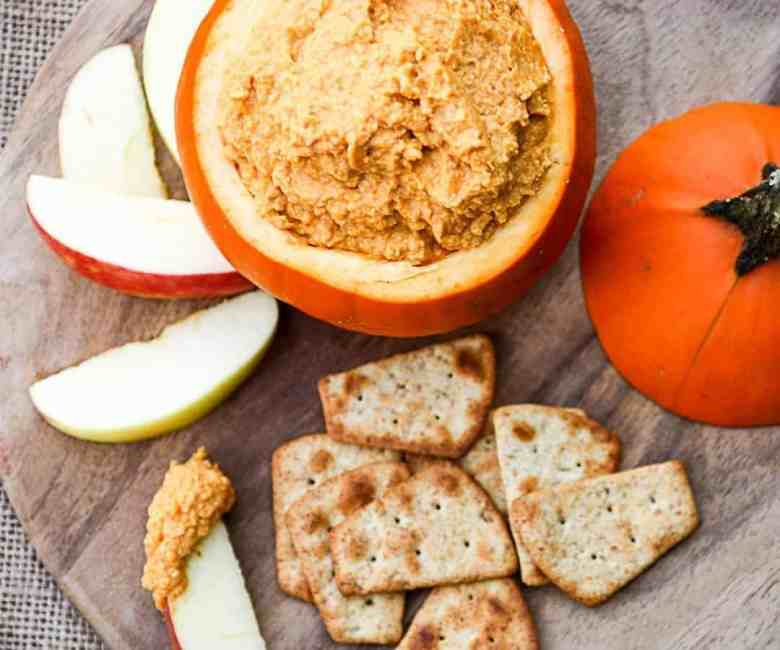 A hollowed-out pumpkin filled with dip, with apple slices and crackers