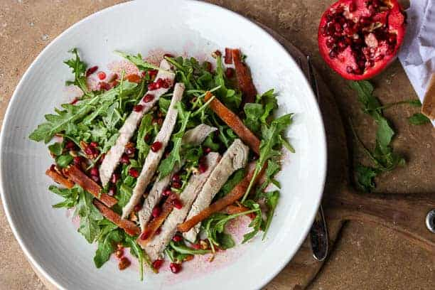 A bowl of salad on a plate, with Pomegranate and Turkey Breast