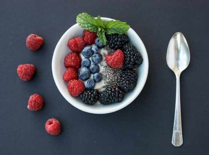 A bowl of fruit on a plate, with Berries