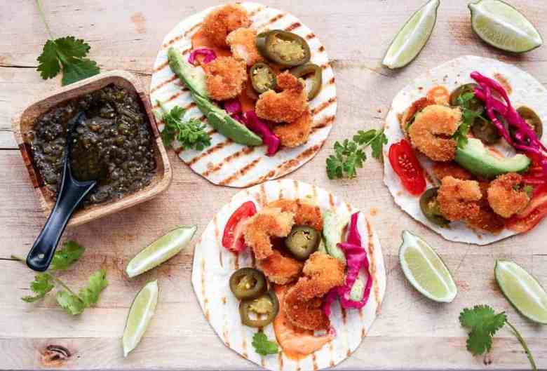 3 Coconut Shrimp Tacos with jalapeno slices, avocado slices and lime wedges