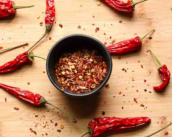 A dish of crushed dried chile peppers and whole chiles on a wooden table