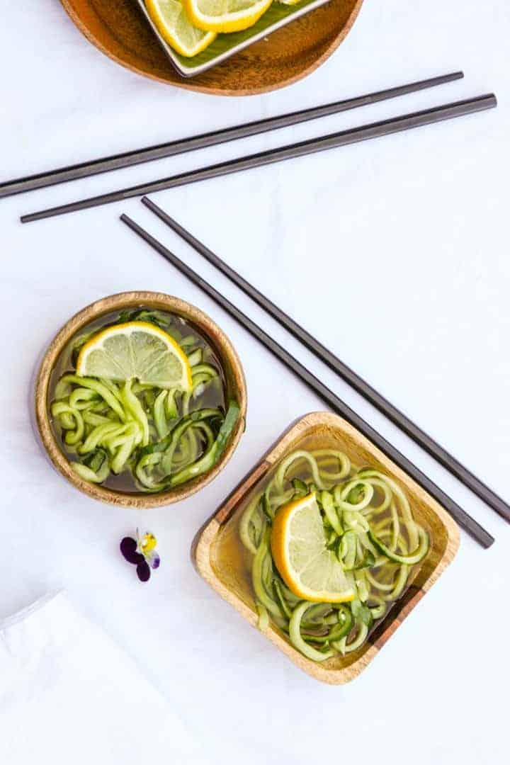 2 wooden bowls of sunomono salad and two sets of black chopsticks