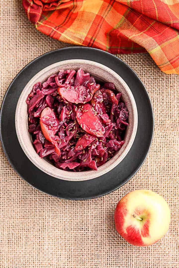 A bowl of food, with Red cabbage and an apple on a table