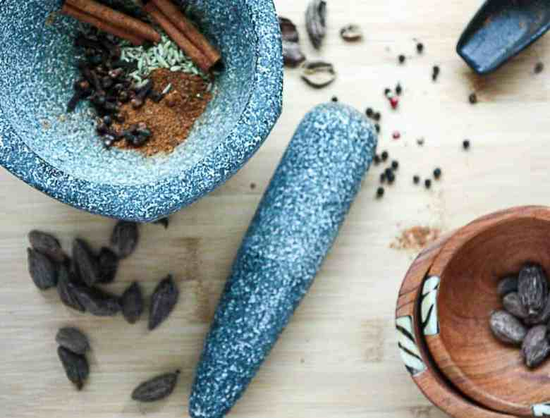 A mortar and pestle with spices ready for grinding
