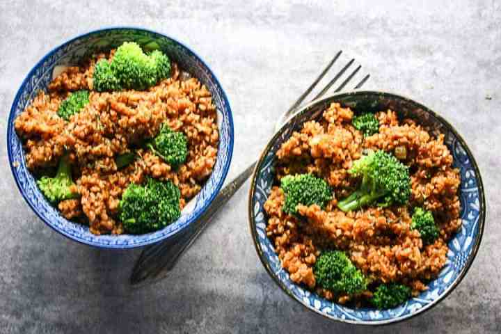 Two bowls of bulgur pilaf with a fork