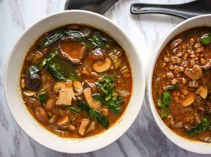 Two bowls of mushroom soup with barley