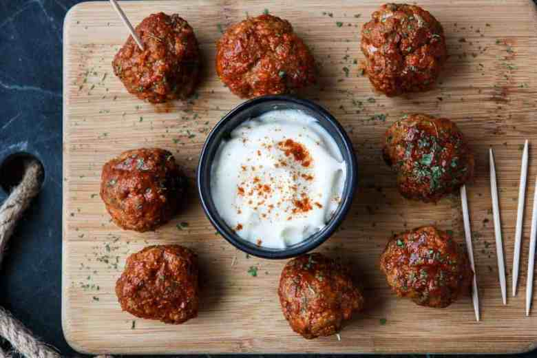 Eight Cajun Turkey Meatballs on a wooden platter with a dish of ranch dip