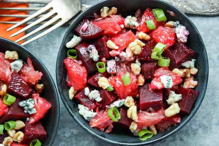 Salad with nuts and blue cheese crumbles in black bowls