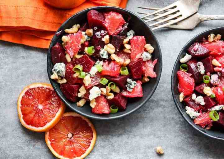 Beet salad with grapefruit slices and blue cheese crumbles in black bowls