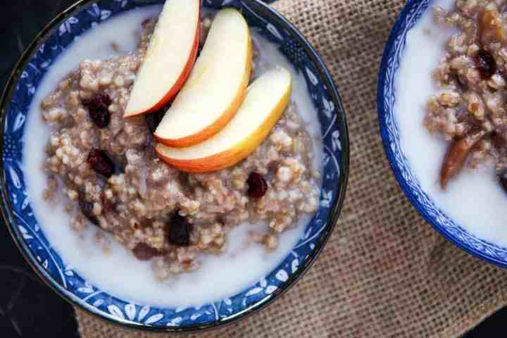 A bowl of oatmeal, with apple slices
