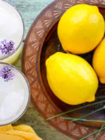 A bowl of lemons on a table, with Lemonade