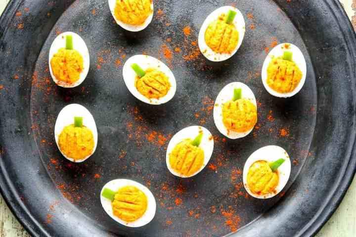 Pumpkin shaped deviled eggs on a black plate