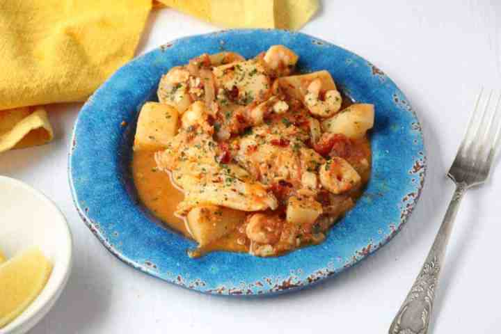 Spanish fish stew on a blue plate