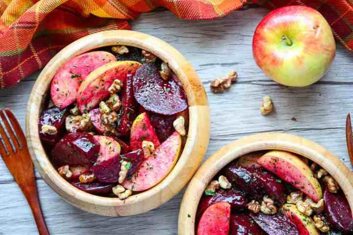 Two wooden salad bowls with roasted beet, apple & walnut salad, and an apple and wooden fork.