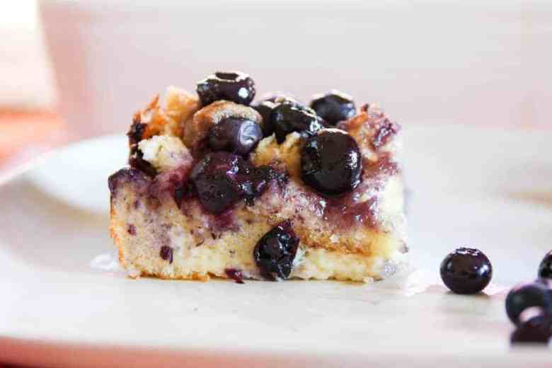 A close up of a piece of breakfast casserole on a plate, with Blueberries
