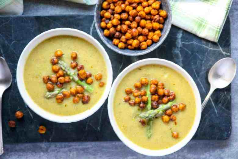 Two bowls of soup and a bowl of roasted chickpeas on a countertop