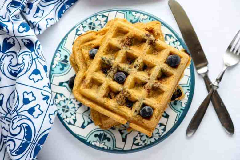 Blueberry coconut waffles on a blue and white patterned plate with a blue & white napkin, fork, and knife