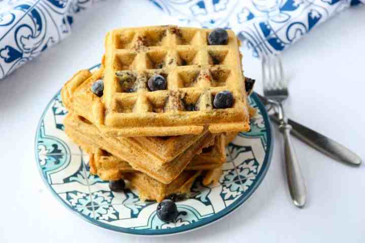 A stack of waffles on a plate, with blueberries