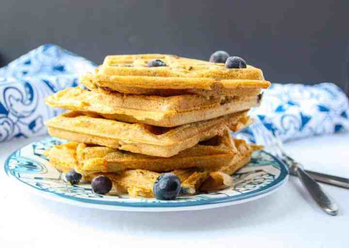 Five blueberry waffles stacked on a blue & white plate
