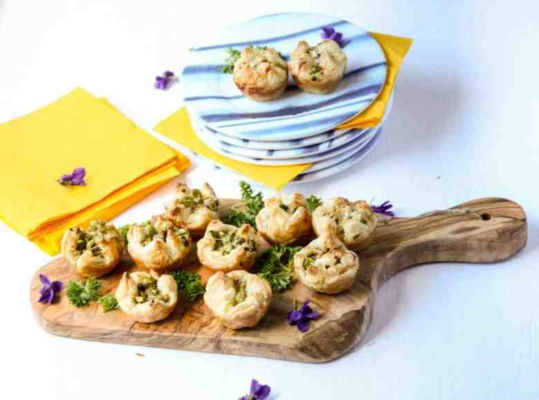 Asparagus puff pastry appetizers on a wooden serving board.