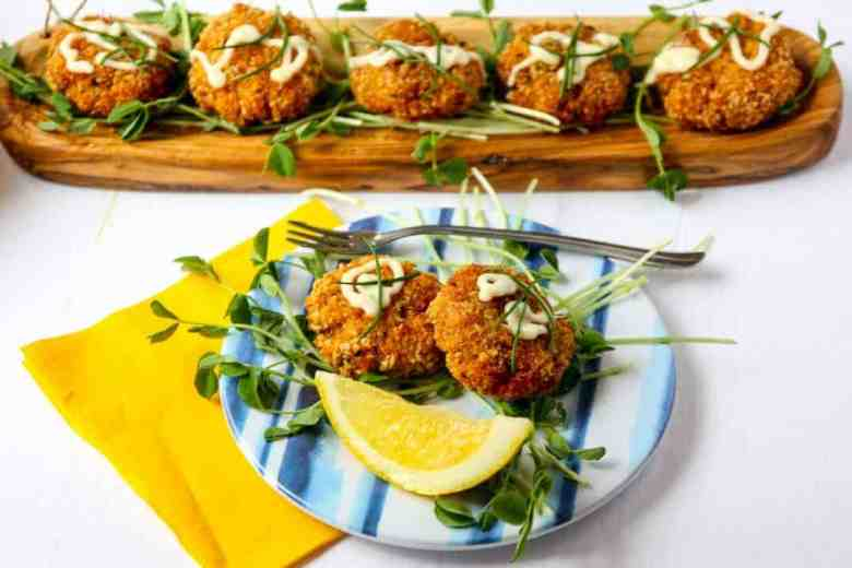 A wooden tray of Cajun Crab Cakes on a bed of pea shoots.
