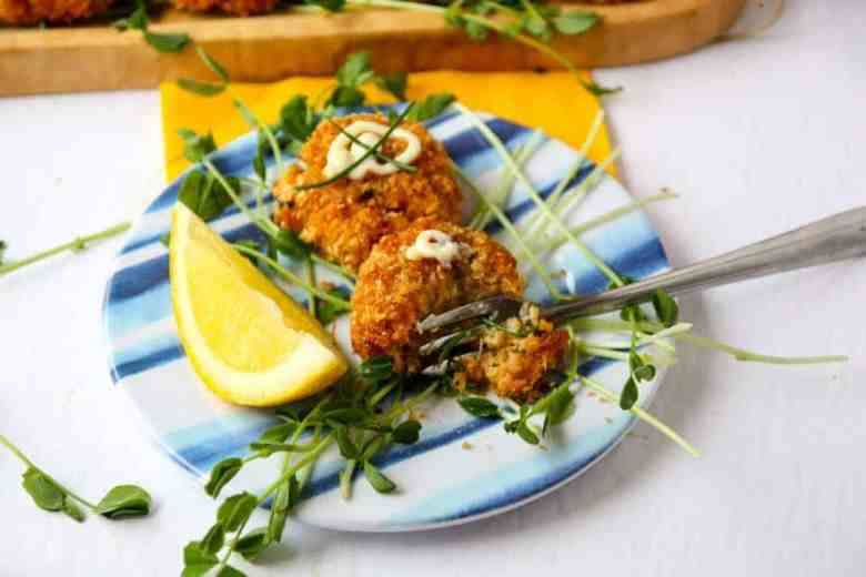 Two Cajun Crab Cakes on a small blue & white plate with peas shoots and a lemon wedge.