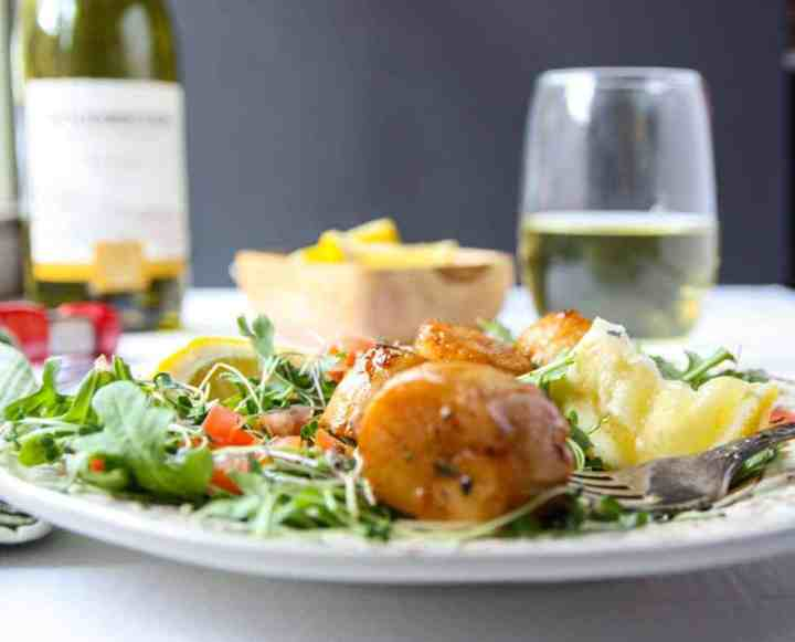 A close up of a plate of food on a table, with Scallops and Wine