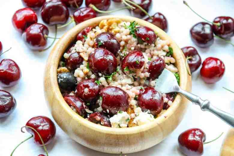 A bowl of salad with cherries and a fork