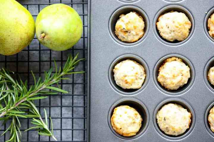 Mini muffins in a pan on a rack, with a pear