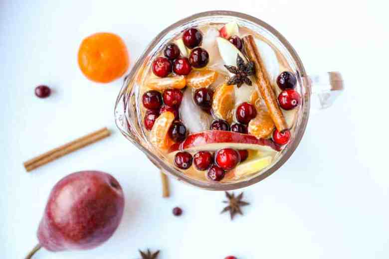 Top down view of carafe of sangria filled with cinnamon sticks, apple slices, orange slices, and cranberries