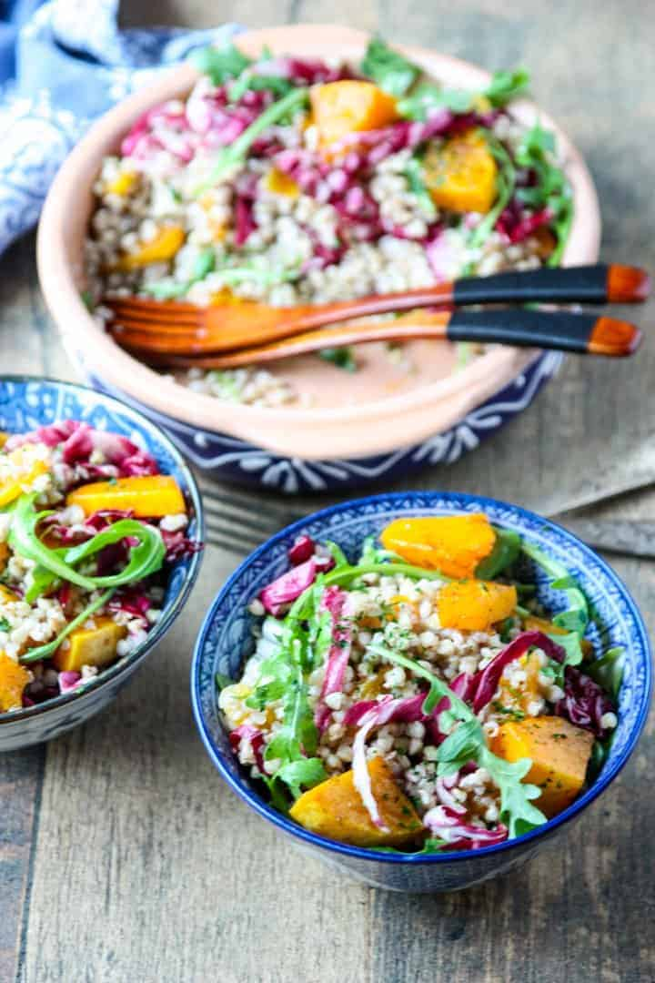Two blue & white bowls of butternut buckwheat salad and a serving bowl half full of salad with two wooden forks