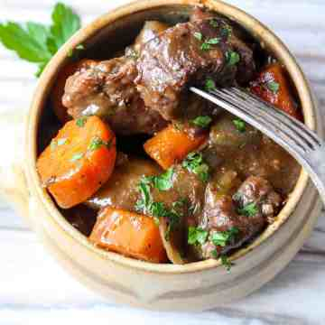 A bowl of Beef Stew with carrots and chunks of beef garnished with parsley.