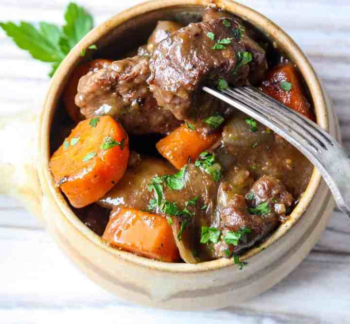 A bowl of stew with beef and carrots in gravy.