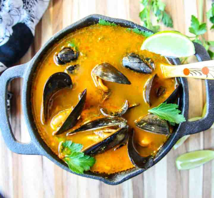 A pot of shellfish in orange broth on wooden table