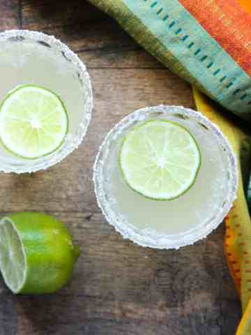 Two cocktails on a table with lime