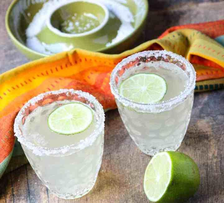 2 salt rimmed glasses of prosecco margarita cocktails with lime slices