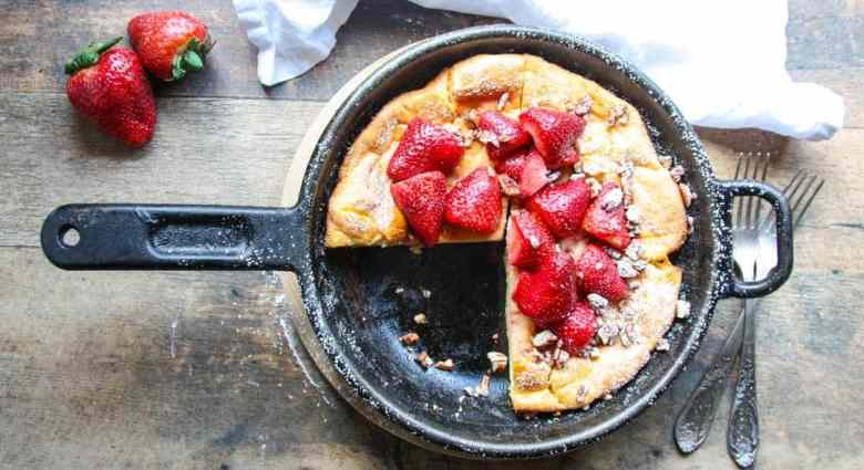 A large pancake in a pan on a table, with Strawberries
