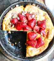 A large pancake in a pan on a table, topped with strawberries.