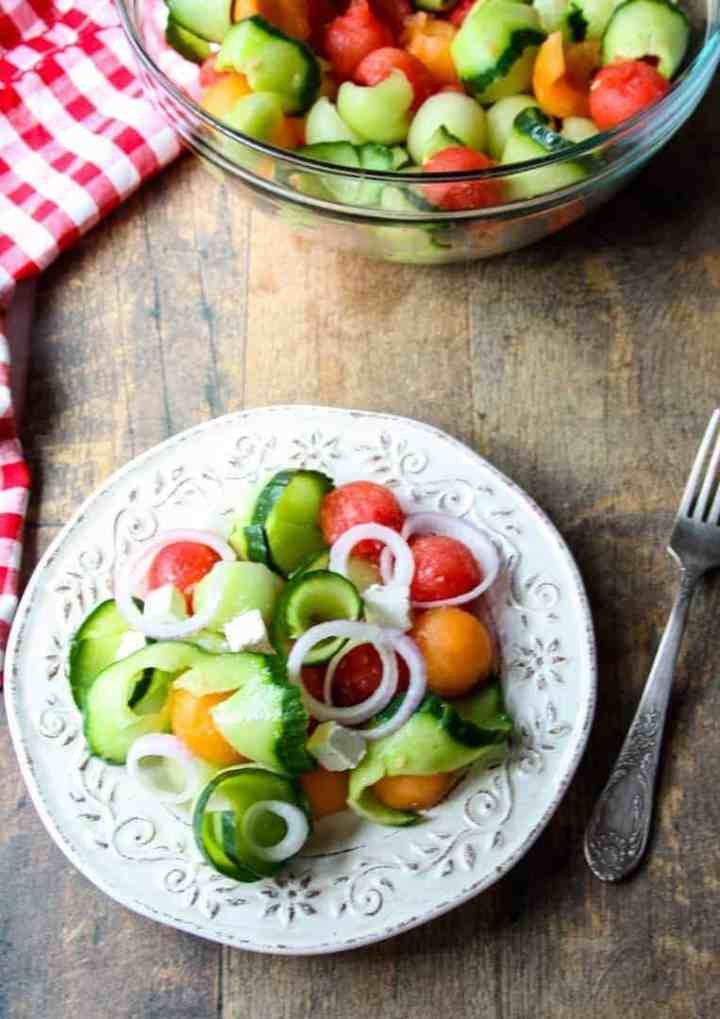 A bowl of food sitting on top of a wooden table, with Salad and Cucumber