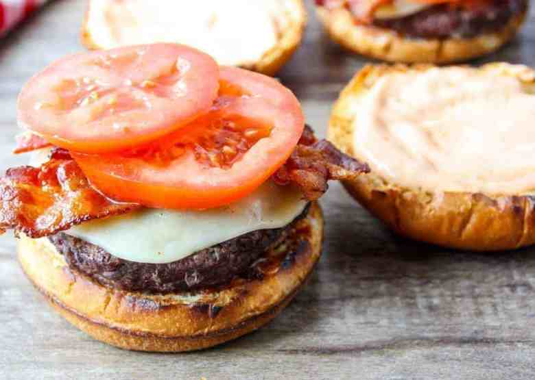 A burger topped with bacon, cheese and tomato