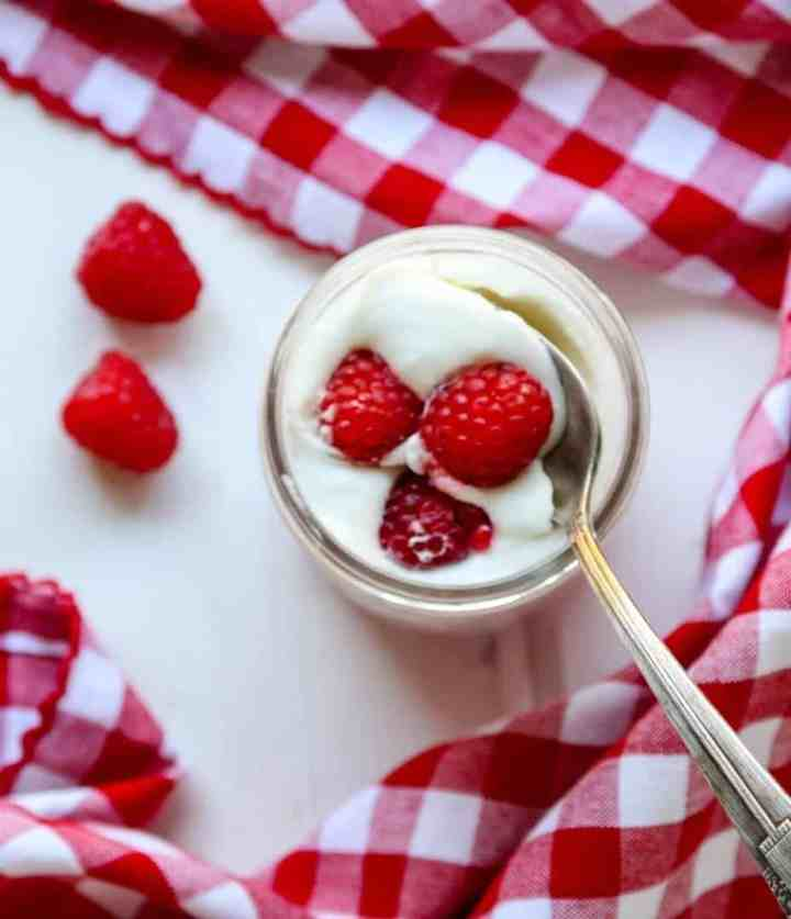 A close up of a jar of mousse with berries